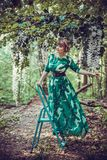 Beautiful girl in a green long dress is standing on the stairs stepladder in the forest. royalty free stock image