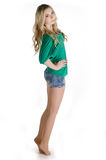 Beautiful girl in a green shirt standing on toes Royalty Free Stock Images