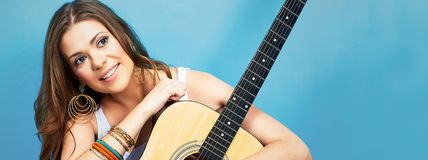 Beautiful girl with guitar against blue background. Long hair Stock Photos