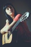 Beautiful girl with guitar. Looking away Royalty Free Stock Photos