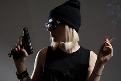 Beautiful girl with a gun in his hand and smoking a cigarette. Royalty Free Stock Photo