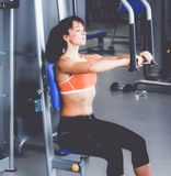 Beautiful girl at the gym exercising on trainers.  Royalty Free Stock Image