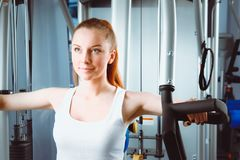 Beautiful girl at the gym exercising on trainers. Beautiful girl.  Stock Images