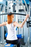 Beautiful girl at the gym exercising on trainers. Beautiful girl.  Royalty Free Stock Photos