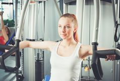 Beautiful girl at the gym exercising on trainers. Beautiful girl.  Stock Image