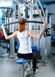 Beautiful girl at the gym exercising on trainers Stock Photos
