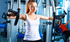 Beautiful girl at the gym exercising on trainers Stock Photo