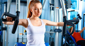 Beautiful girl at the gym exercising on trainers Stock Photography
