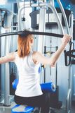 Beautiful girl at the gym exercising on trainers. Beautiful girl.  Stock Photo