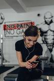 Beautiful girl at the gym listening to music Stock Image