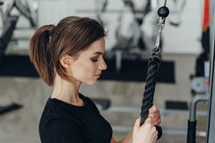 Beautiful girl at the gym on a simulator Royalty Free Stock Photo