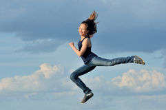 Beautiful girl in gymnastic jump against blue sky Stock Photos