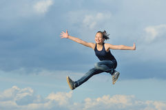 Beautiful girl in gymnastic jump against blue sky Stock Photography