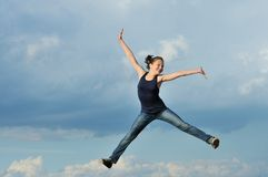 Beautiful girl in gymnastic jump against blue sky Royalty Free Stock Photos