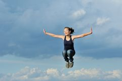 Beautiful girl in gymnastic jump against blue sky Royalty Free Stock Image