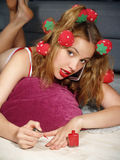Beautiful girl in hair curlers  lies on a floor Stock Photo