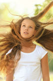 Beautiful girl with hair that wind. Young beautiful girl with hair that wind is blowing, against green summer garden stock photo