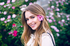 Beautiful girl with hairstyle and flower in hair smiling looking at camera and standing near natural flower wall Royalty Free Stock Image