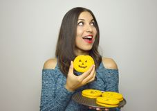 Beautiful girl with halloween homemade cookies looking copy space on gray background Royalty Free Stock Photo