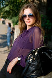 Beautiful girl with a handbag and dark glasses Stock Images