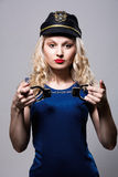 Beautiful girl with handcuffs and a police cap Stock Images