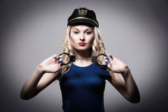 Beautiful girl with handcuffs and a police cap Royalty Free Stock Images