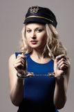 Beautiful girl with handcuffs and a police cap Stock Photo