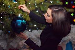 A beautiful girl hangs on a Christmas tree a big blue ball on Ne Royalty Free Stock Photo