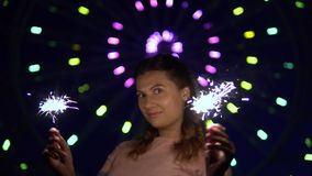 A beautiful girl is happy with a holiday with fireworks in her hands. slow motion. HD. A beautiful happy girl is happy with a holiday with fireworks in her hands stock video footage