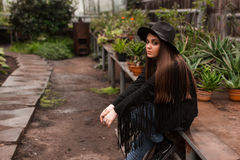 Beautiful girl in a hat on background of the botanical garden Royalty Free Stock Image