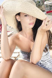 Beautiful girl with hat at the beach sitting on a lounge chair. Royalty Free Stock Images