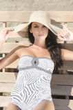Beautiful girl with hat at the beach sitting on a lounge chair. Stock Image