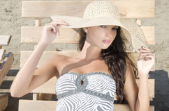 Beautiful girl with hat at the beach sitting on a lounge chair. Royalty Free Stock Image