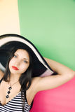 The beautiful girl in a hat on a colour background Royalty Free Stock Photos