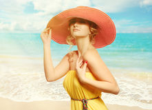 Beautiful girl in a hat enjoying the sun on the beach. Royalty Free Stock Image