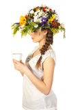 Beautiful girl in hat of flowers and cup of tea Royalty Free Stock Photos