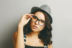 Beautiful girl in a hat and glasses. Stock Photos