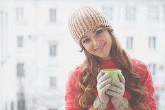 Beautiful girl in a hat and gloves, drinking hot tea Royalty Free Stock Photography