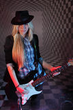 Beautiful girl in hat with guitar in studio in smoke. Royalty Free Stock Image