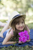 Beautiful girl with a hat lying on the grass and holding a bouqu. Et of flowers and enjoy nature Stock Photos