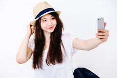 Beautiful girl in the hat makes selfie on the floor. In the Studio on a white background Stock Image