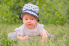 Beautiful girl in hat, panama having fun outdoor. Toddler lying in the grass. stock images