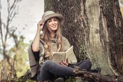Girl in a hat reading a book in autumn forest Royalty Free Stock Photo