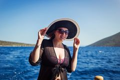 Beautiful girl in hat relaxing on the boat and looking at the is Royalty Free Stock Photography