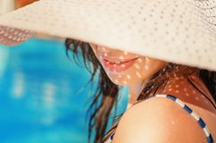Beautiful girl in a hat relaxing near a swimming pool Stock Photo