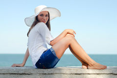 Beautiful girl in hat resting outdoors by the sea Royalty Free Stock Photography