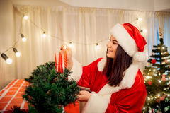 Beautiful girl in the hat of Santa Claus lighting candles on the royalty free stock photography