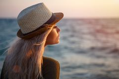Beautiful girl in hat by the sea at sunset stock photo
