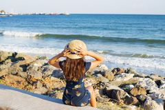 Beautiful girl in a hat sits near the sea on stones.  Royalty Free Stock Images