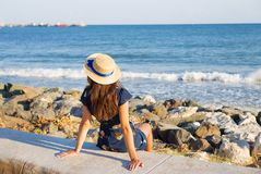 Beautiful girl in a hat sits near the sea on stones.  Stock Photos